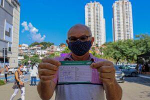 Homem exibe cartão após ser vacinado no Shopping Taboão