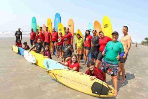 Alunos aprendem as noções básicas de surfe e o respeito à natureza, na praia dos Pescadores