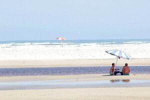 Praia ainda é pouco frequentada e maior movimento é registrado aos domingos; visitantes desfrutam de piscinas naturais e podem se banhar no rio ou no mar