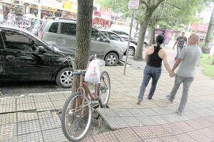 Sem estacionamento apropriado para as bicicletas, ciclistas são obrigados a prender o transporte em árvores e postes e reclamam de roubos constantes na região