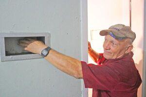 O mestre de obras João de Souza mostra a pequena abertura na porta da antiga solitária onde mora há dez anos