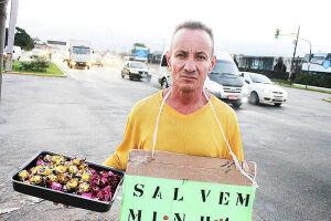 Guile, o conhecido vendedor da entrada de Santos está com uma placa pedindo ajuda para voltar a enxergar