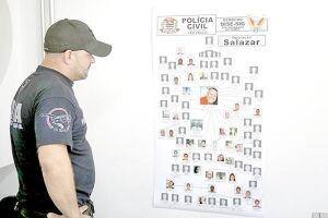 Policial observa organograma em que o líder da quadrilha aparece ao centro