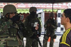 Moradores da favela passam por registro e foto realizados pelo exército.