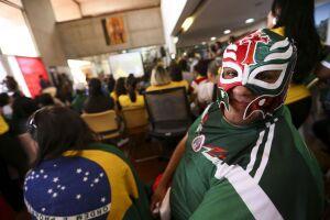 O torcedor mexicano com máscara de atleta de luta livre divide seu espaço na Embaixada do México ao lado de brasileiros
