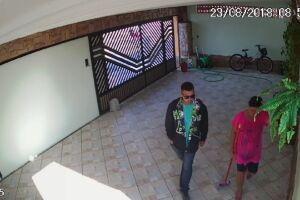 Um dos ladrões rende a empregada doméstica da casa